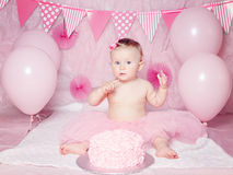 Portrait of cute adorable Caucasian baby girl with blue eyes in pink tutu skirt celebrating her first birthday. With gourmet cake and balloons looking in camera Royalty Free Stock Photos