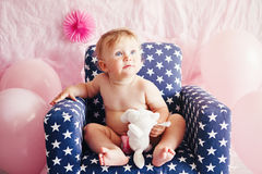 Portrait of cute adorable Caucasian baby girl with blue eyes sitting in blue children kids armchair with white stars celebrating Stock Photos