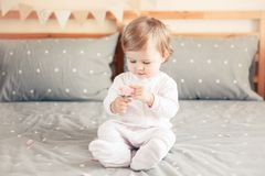 Caucasian blonde baby girl in white onesie sitting on bed in bedroom. Portrait of cute adorable Caucasian blonde smiling baby girl in white onesie sitting on bed Royalty Free Stock Images