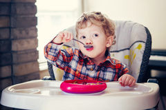 Portrait of cute adorable Caucasian child kid boy standing in high chair with leg on table early morning. Portrait of cute adorable Caucasian child kid boy stock images