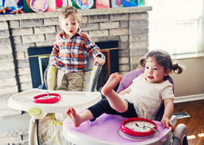 Portrait of cute adorable Caucasian children twins siblings sitting in high chair eating cereal early morning Stock Image