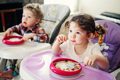 Portrait of cute adorable Caucasian children twins siblings sitting in high chair eating cereal early morning Stock Photo