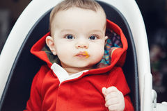 Portrait of cute adorable Caucasian little baby boy sitting in high chair in kitchen eating meal puree Royalty Free Stock Image