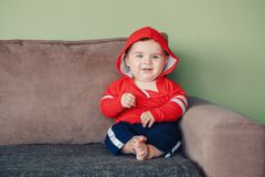 Seven months child sitting on couch at home looking in camera Stock Image