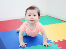 Portrait of cute adorable Caucasian smiling baby boy girl lying on floor in kids room looking in camera. Natural window light, lifestyle stock images