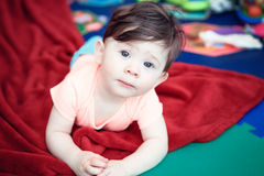 Portrait of cute adorable Caucasian smiling baby boy girl lying on floor in kids room. Looking in camera, natural window light, lifestyle royalty free stock photo