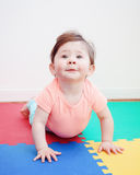 Portrait of cute adorable Caucasian smiling baby boy girl lying on floor in kids room. Looking in camera, natural window light, lifestyle royalty free stock photography