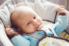 Portrait of cute adorable funny white Caucasian blond little baby boy newborn with blue grey eyes in blue clothes Royalty Free Stock Image