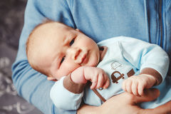 Portrait of cute adorable funny white Caucasian blond little baby boy newborn lying on parent hands Stock Photos