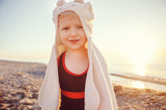 Portrait of cute adorable happy smiling toddler little girl with towel on beach making poses faces having fun Stock Image