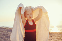 Portrait of cute adorable happy smiling toddler little girl with towel on beach making poses faces having fun Stock Images
