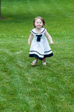 Portrait of a cute adorable little girl child in dress running on grass Royalty Free Stock Photography