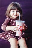 Girl wearing dress with hearts sitting on couch. Portrait of cute adorable little girl wearing dress with hearts sitting on couch. Child drinking from funny Stock Photo