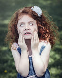 red-haired Caucasian girl in blue dress making funny scary silly faces royalty free stock photos