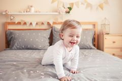 Caucasian blonde baby girl in white onesie sitting on bed in bedroom
