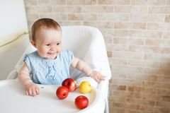 Portrait of cute adorable smiling laughing Caucasian child kid girl sitting in high chair eating apple fruit. Everyday lifestyle. copy space stock photo