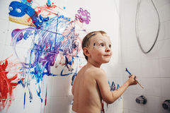 Portrait of cute adorable white Caucasian little boy playing and painting with paints  on wall in bathroom Stock Image