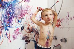 Portrait of cute adorable white Caucasian little boy playing and painting with paints  on wall in bathroom Royalty Free Stock Photography