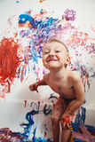 Portrait of cute adorable white Caucasian little boy playing and painting with paints  on wall in bathroom. Having fun, lifestyle childhood concept Stock Photography