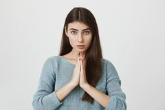 Portrait of cute adult woman with long hair and angel look, glancing at camera while holding hands in pray or beg. Standing over gray background. Girlfriend Royalty Free Stock Photography