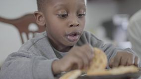 Portrait of cute african american child boy with dirty lips after milk playing with cookies sitting by the table in. Portrait of nice african american child boy stock footage