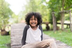 Portrait of a cute African american little boy smiling at nature park. stock photo