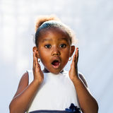 Portrait of cute African girl with shocking face expression. Against light background Royalty Free Stock Photography