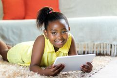 Portrait of cute african girl with tablet at home. Close up portrait of cute little african girl with ponytail laying on carpet in lounge with tablet Royalty Free Stock Images