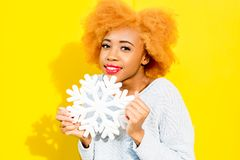 Portrait of a woman with artificial snowflake on the yellow background. Portrait of a cute african woman in blue sweater holding an artificial snowflake on the royalty free stock photo