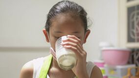 Portrait cute in apron wearing protective mask and drinking milk in quarantine to protect society from the disease.
