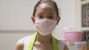 Portrait cute in apron wearing protective mask in quarantine to protect society from the disease. Female teenager staying home.