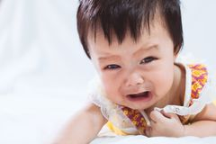 Portrait of cute asian baby girl crying in her bedroom royalty free stock image