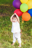 Portrait of cute Asian child with balloons clapping her hands Royalty Free Stock Photo