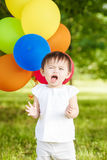 Portrait of cute Asian child with balloons clapping her hands Royalty Free Stock Image