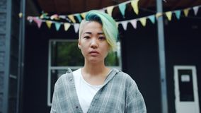 Portrait of cute Asian girl hipster with serious face standing outdoors. And looking at camera. Beautiful young people, modern city and emotions concept stock footage