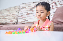 Portrait of cute asian little girl playing brick on table at hom Royalty Free Stock Image