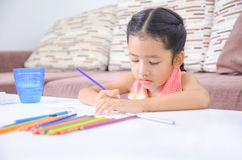 Portrait of cute asian little girl Thai painting the color at ho Royalty Free Stock Photos