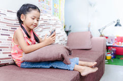 Portrait of cute asian Thai little girl playing mobile phone at Royalty Free Stock Image