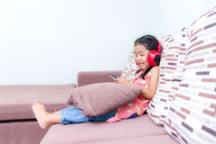 Portrait of cute asian Thai little girl using mobile phone and r Royalty Free Stock Photo