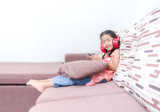 Portrait of cute asian Thai little girl using mobile phone and r Stock Photo