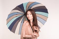 Portrait of cute asian woman under striped umbrella on white background royalty free stock photos