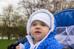 Portrait of cute baby with angel eyes sitting in stroller. Age of the baby is 6 months. Stock Photo
