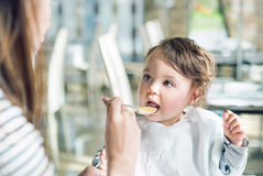 Portrait of a cute baby being fed by her mom Stock Image