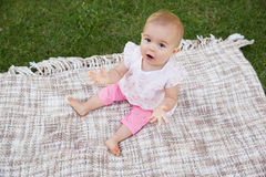 Portrait of a cute baby on blanket at park. High angle portrait of a cute baby sitting on blanket at the park Royalty Free Stock Photography