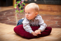 Portrait of cute baby boy child kid indoor. Happy childhood. Portrait of cute pensive baby boy. Sleepy child kid lying on the pillow. Indoor. At home Royalty Free Stock Images