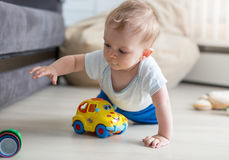 Portrait of cute baby boy crawling on floor and playing with toy Stock Photos