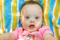 Portrait of Cute baby boy with Down syndrome lying on blanket in summer day on nature Royalty Free Stock Photo