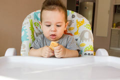 Portrait cute baby boy eating child biscuit the first food for babies 10 months. toddler boy learning to live with teeth solid foo stock photography