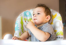 Portrait cute baby boy eating child biscuit the first food for babies 10 months. toddler boy learning to live with teeth solid foo Stock Photo