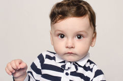 Portrait of a cute baby boy looking at camera with big eyes curious. Royalty Free Stock Image